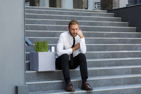 An unhappy young manager in a white shirt is fired from his job. A sad worker sits on the steps of a business center after layoffs. Crisis and unemployment.