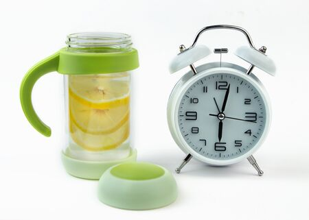Alarm clock and a detox glass of water with lemon on a glass table. Wake up early in the morning by the alarm bell. Intermittent fastind diet concept. Фото со стока