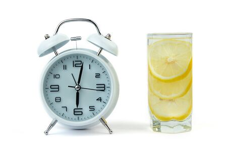 Alarm clock and a detox glass of water with lemon on a glass table. Wake up early in the morning by the alarm bell. Intermittent fastind diet concept. Фото со стока - 130921932