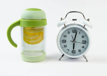 Alarm clock and a detox glass of water with lemon on white backgrounf. Wake up early in the morning by the alarm bell. Reklamní fotografie