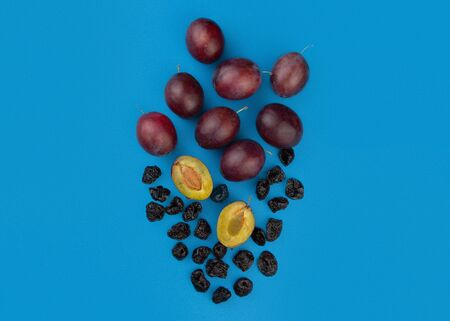 Fresh ripe plums, whole and halves, and dried prunes on a blue background.