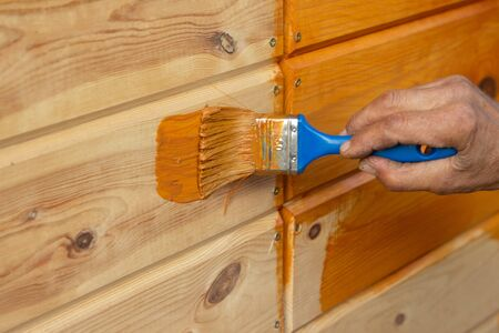 Mans Hand holding a brush applying varnish paint on a wooden surface. Brush on wooden background. Board half painted. 写真素材
