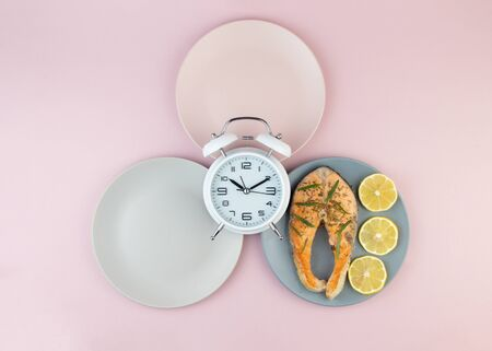 Intermittent fasting concept with empty colorful plates. Time to lose weight , eating control or time to diet concept.Healthy eating food low carb keto ketogenic diet.
