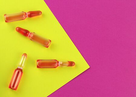 Ampoule and syringe with red liquid on colorful background. Flu vaccination. Catch-up immunization. Imagens