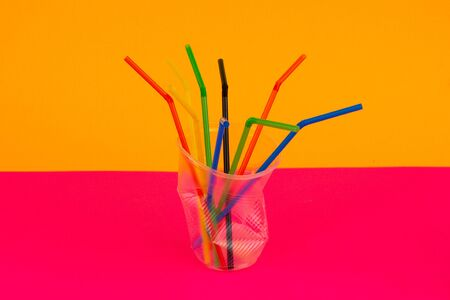 Empty crumpled plastic disposable cup with colorful straws on a multi-colored background. Concept of garbage and Environmental pollution.