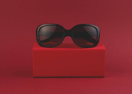 Fashionable sunglasses on a box on a red background. Minimal style. Minimalist fashion photo. Front view. Standard-Bild - 134659103