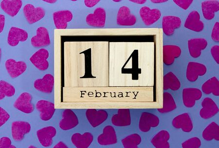 Wooden calendar cube show of February 14 on background with red hearts. Flat lay.