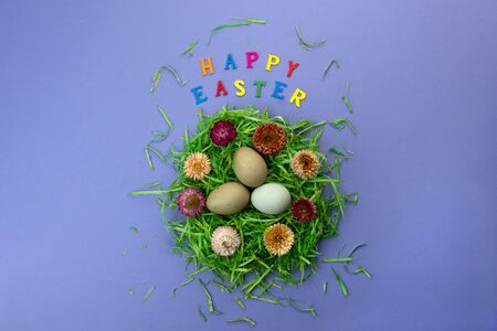 Easter composition with nest, eggs and colorful letters on violet background. Text Happy Easter. Flat lay. Stock Photo