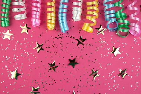 Carnaval festive curling colorful paper streamer decorations on pink background. Party or carnival concept