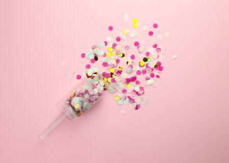 Popper con confeti de papel multicolor sobre fondo rosa. Disparos de confeti.