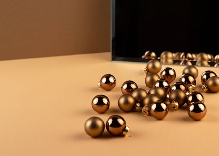 Reflection of group of christmas balls and shadow from balls in a mirror on beige surface. Minimalist geometric style.