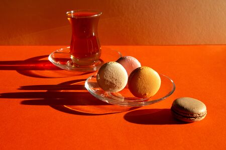 Traditional Turkish glass tea with sweets casts a dark shadow. French desserts Macarons. Minimal composition on red-orange color background.