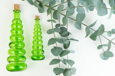 Glass green bottles and a branch of eucalyptus on a white background. Essential oils for spa.