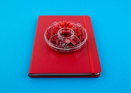 Red Business notebook and stationery on blue table. Back to school or workplace abstract background. Minimal composition.