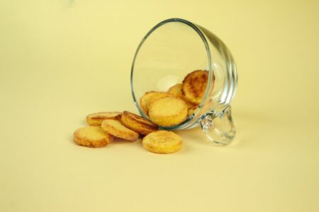 Appetizing homemade cookies in a glass inverted mug on a yellow background. Breakfast time. Minimalist composition Stock Photo