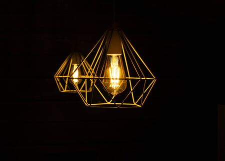 Modern metal lampshade with a yellow led lamp isolated on a black background. Abstract interior fragment.
