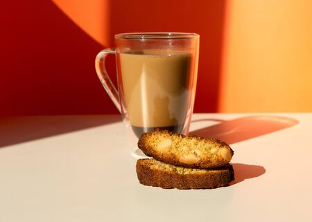 Biscotti almond cookies and a cup of coffee on the table on orange background. Geometric minimalist composition with shadow. Front view. Stock Photo