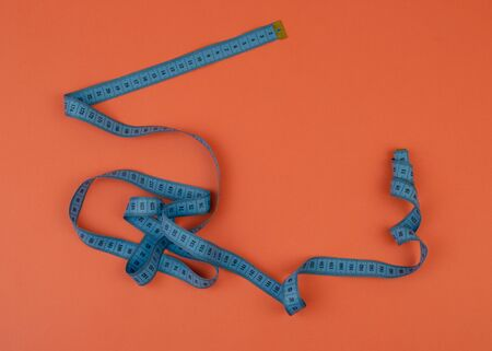 Blue tailor measuring tape on orange background with copy space. Banque d'images