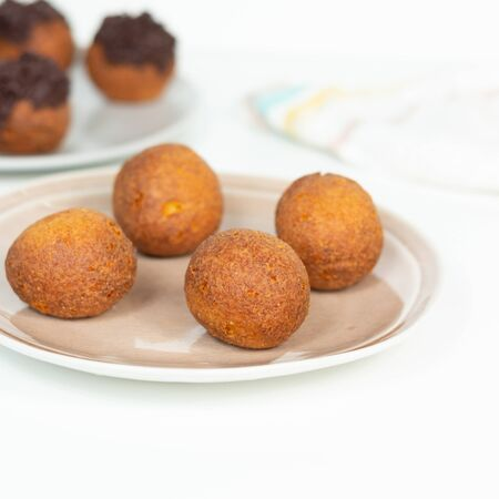 Deep fried bunuelos balls. Creative minimalist composition on a white background. Front view.