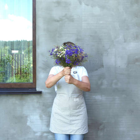 The girl in an apron hides her face behind a bouquet of meadow flowers. The window reflects the sky and the fence. Florist makes a bouquet.