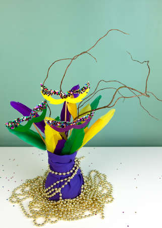 Mardi Gras decoration. Bouquet of multicolored feathers and masks in violet cloth vase. Party invitation. Shrove Tuesday, Fat Tuesday. DIY