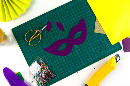DIY colored Mardi Gras mask. Workplace with colored paper, feathers, confetti, glitter and scissors. Party preparation. Shrove Tuesday, Fat Tuesday. Flat lay