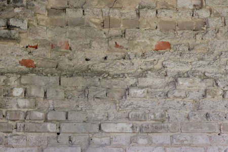 Background of old, destroyed, painted brickwork of a building.