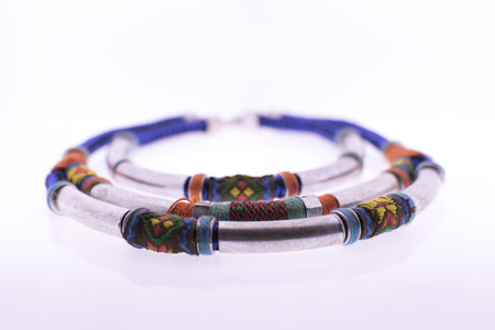 basic material: ?olorful necklace with metal inserts - the basic material - thread and aluminum alloy on white background