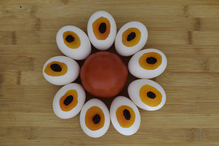 limon: Tomato eggs dried apricots raisins in one flower on wooden plank kitchen composition Stock Photo