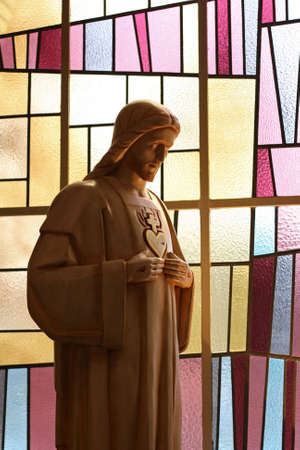 A jesus figure with punctured hands and heart in front of a modern stained glass window