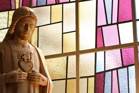 irridescent: A jesus figure with punctured hands and heart in front of a modern stained glass window