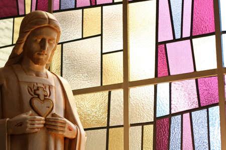 pentimento: Un jesus cifra con punta in mani e il cuore di fronte a una moderna vetrata