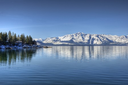 with reflection: A reflection of Elk Point on Lake Tahoe from Marla Bay with Pyramid Peak and Mount Price reflecting in the background.