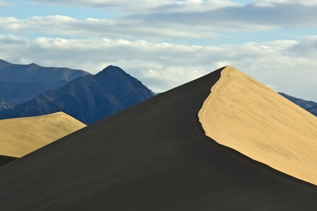 Contrasting light and shadows on sand dunes and mountains in Mesquite Flat, Death Valley National Park, California. Stock Photo - 7605330
