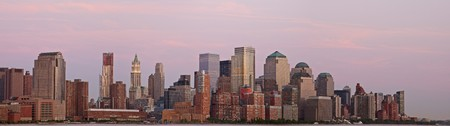 A panoramic view of the downtown Manhattan skyline at sunset.