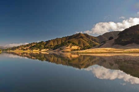 A morning reflection on Uvas Reservoir of the rolling hills and chaparral of the central California. Stock Photo - 7633411