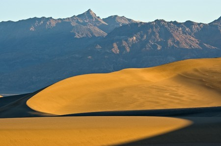 First light hits the sand dunes on Mesquite Flat showing curved patterns of light and shadows underneath towering mountains in Death Valley National Park, California.