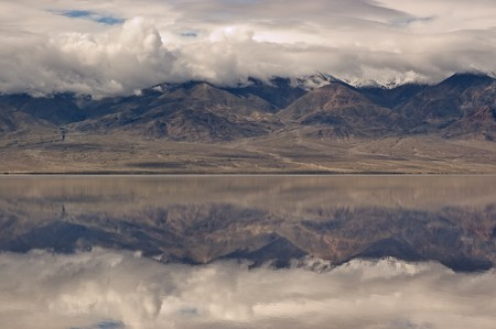 A reflection of mountains and dramatic sky on the rarely water filled valley in Badwater, Death Valley National Park, California.