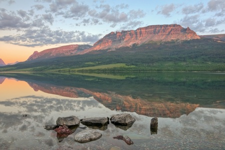 A reflection of the East Flattop Mountain and Napi Point on Saint Mary Lake in Glacier National Park, Montana.