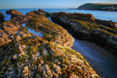 The warm sun catches the layered rocks in Spooners Cove in Montana De Oro State Park. Stock Photo