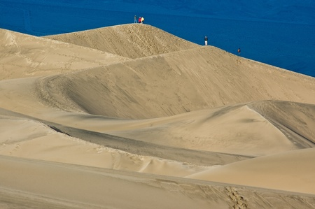 Early morning hikers ascend the dune peaks in Mesquite Flat Sand Dunes, Death Valley National Park, California.