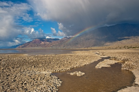 A rainbow appears below a large rain cloud above Badwater in Death Valley National Park, California. photo