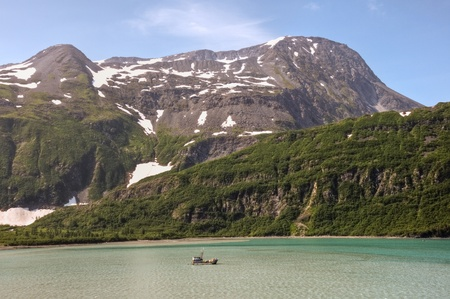 A boat fishes near Whittier, Alaska with the Chugach National Forest in the background.