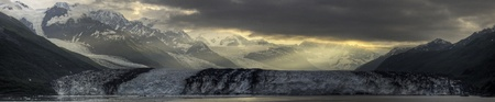 Sunrise breaking through the clouds onto a panorama of the Harvard Glacier.