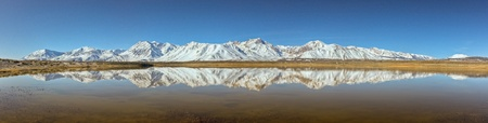 sierras: A beautiful panoramic reflection of the snow capped Eastern Sierras. Stock Photo