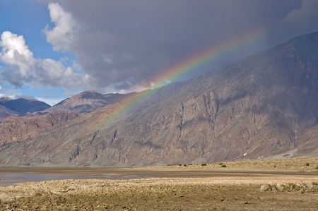 A rainbow appears below a large rain cloud above Badwater in Death Valley National Park, California. Stock Photo - 8914622