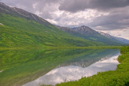 A reflection of a snow-capped mountain in a lake in Chugach National Forest on Kenai Peninsula, Alaska.
