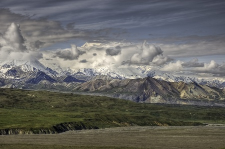 Mount McKinley in dramatic clouds over the tundra covered Muldrow glacier in Denali Natoinal Park, Alaska Stock Photo