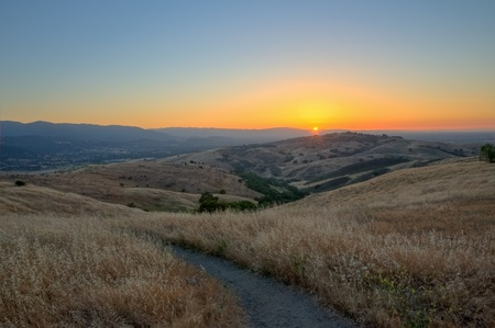 The sun sets on the South San Francisco Bay, Almaden Valley and San Jose from Rocky Ridge trail in Santa Teresa County Park.