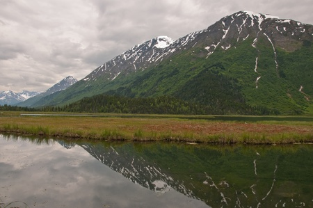 A view of snow-capped mountains and dramatic clouds reflecting off a marsh on the Kenai Peninsula, Alaska. Stock Photo
